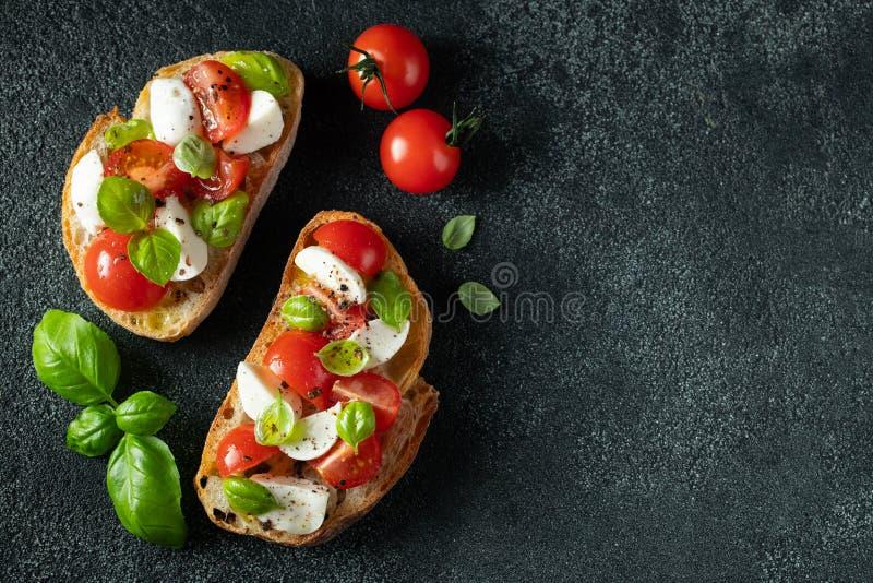 Bruschetta met tomaten, mozarellakaas en basilicum op een donkere achtergrond Traditionele Italiaanse voorgerecht of snack, antip stock afbeeldingen