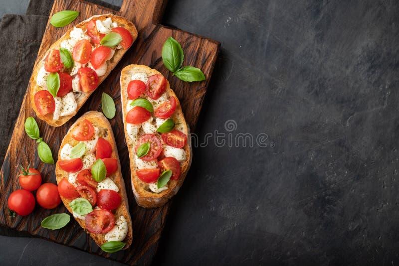 Bruschetta met tomaten, mozarellakaas en basilicum op een scherpe raad Traditionele Italiaanse voorgerecht of snack, antipasto Bo stock foto
