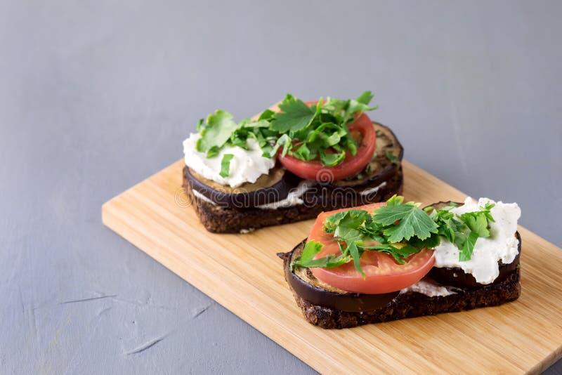 Bruschetta mit gegrilltem Auberginen-Tomaten-Hüttenkäse und frischen aromatischen Kräutern auf hölzernen Tray Delicious Mediterra stockfotos