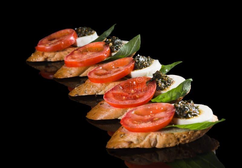 Bruschetta mit Mozzarella, Tomate und Pesto stockfotos
