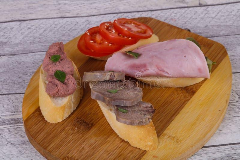 Bruschetta mit Tomate, Schinken und der Zunge lizenzfreies stockfoto