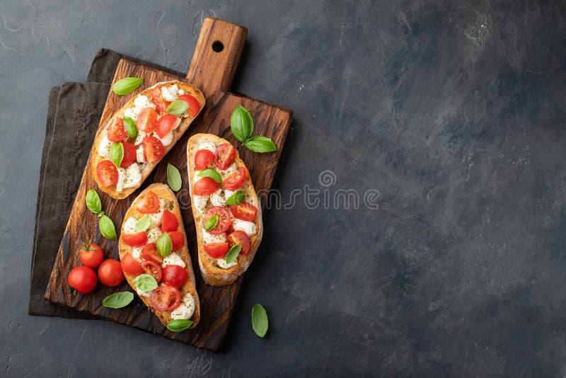 Bruschetta mit Tomaten, Mozzarellakäse und Basilikum auf einem Schneidebrett Traditioneller italienischer Aperitif oder Snack, An lizenzfreie stockfotos