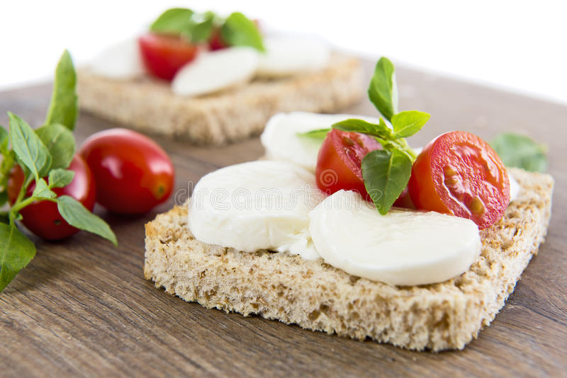 Bruschetta with mozarella and tomatoes. On wood backgraund royalty free stock image