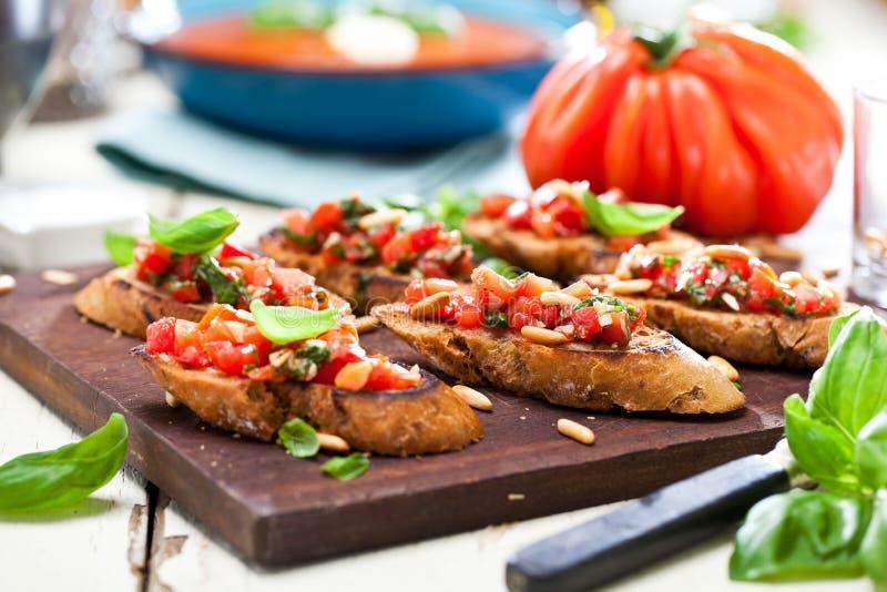 Bruschetta, na plasterkach wznoszący toast baguette garnirujący z basilem obraz stock