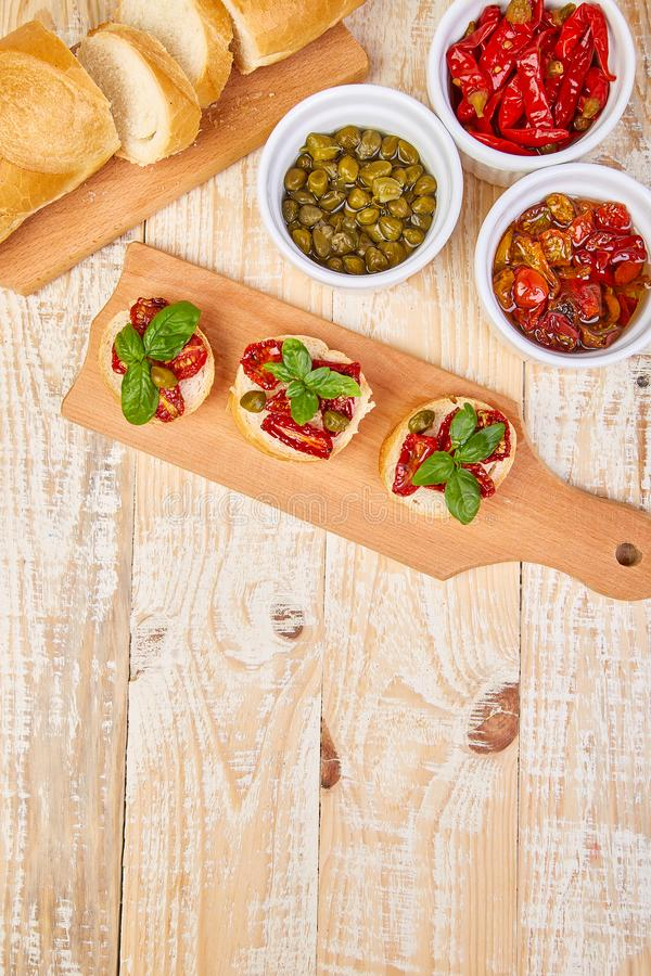 Bruschetta o crostini con i pomodori ed i capperi seccati al sole fotografia stock