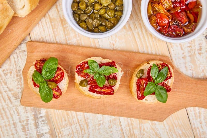 Bruschetta o crostini con i pomodori ed i capperi seccati al sole immagini stock