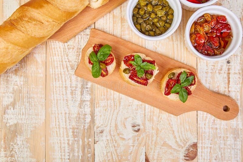 Bruschetta o crostini con i pomodori ed i capperi seccati al sole immagini stock libere da diritti