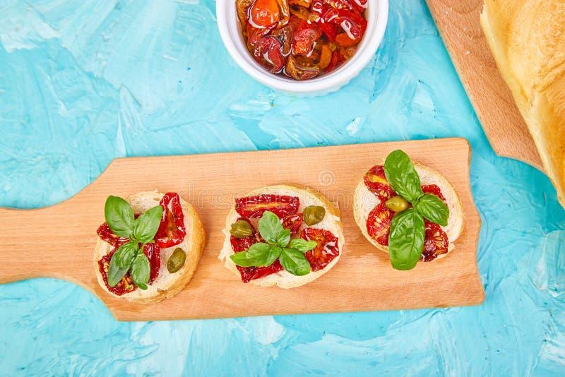 Bruschetta ou o crostini com sol secaram tomates e alcaparras fotografia de stock