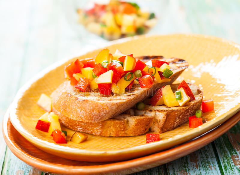 Bruschetta with Peach Salsa. On the plate royalty free stock photo