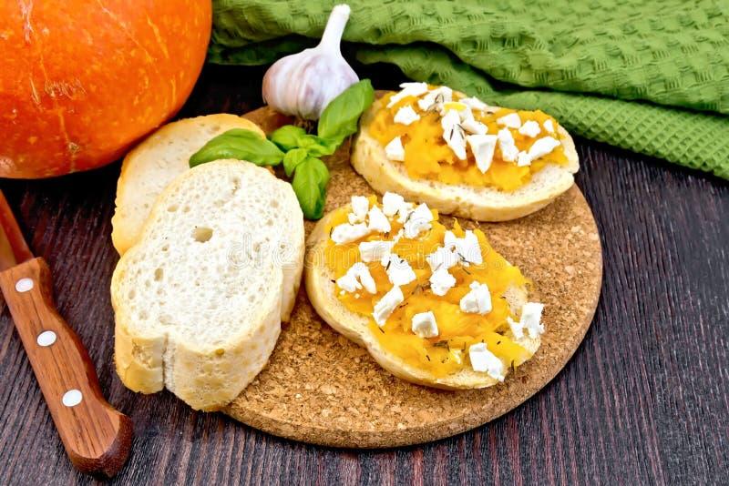 Bruschetta with pumpkin and basil on board stock photography