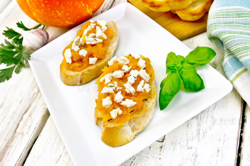 Bruschetta with pumpkin and cheese in plate on board stock image
