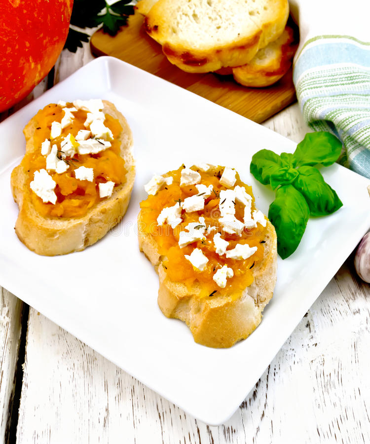 Bruschetta with pumpkin and cheese in white plate on light board stock image