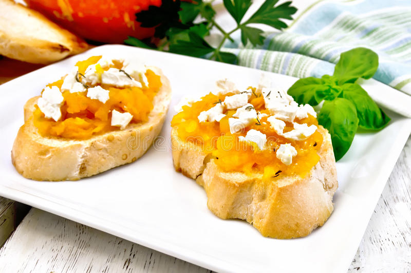 Bruschetta with pumpkin and feta in white plate on board stock photography