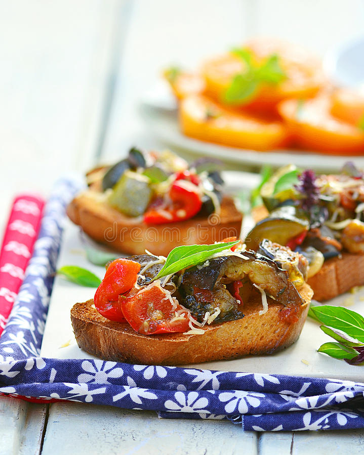 Bruschetta with ratatouille. And yellow tomato salad royalty free stock photo