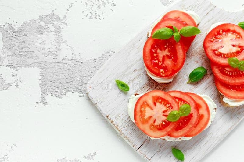 Bruschetta rostat bröd med mjuk ost, basilika och tomater på ett vitt träbräde Italienskt sunt mellanmål, mat royaltyfri bild