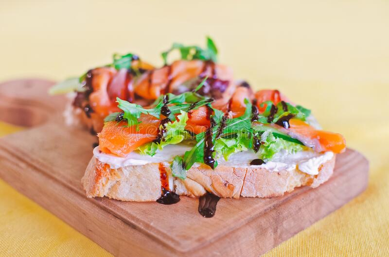 Bruschetta sandwiches with salmon and arugula stock images
