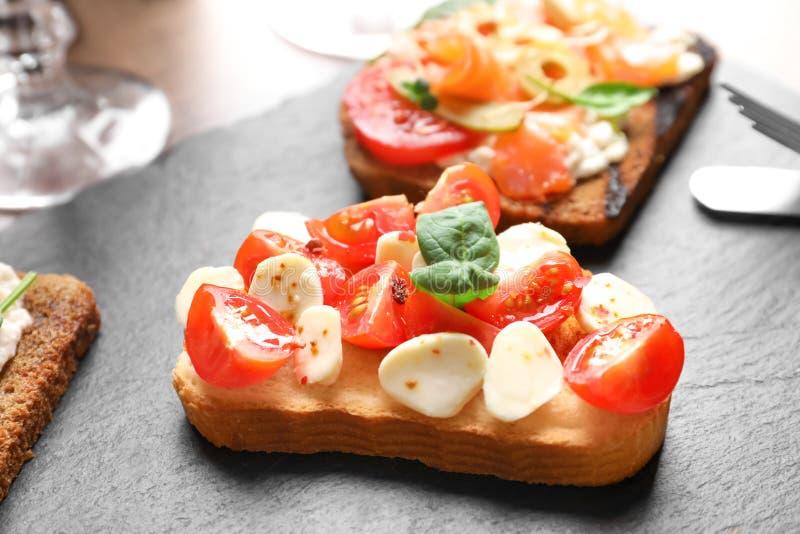 Bruschetta saporita con i pomodori ciliegia e la mozzarella fotografie stock