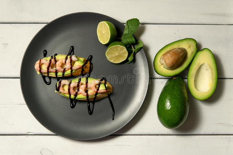 bruschetta with shrimps, avocado and lime on a white wooden background stock images