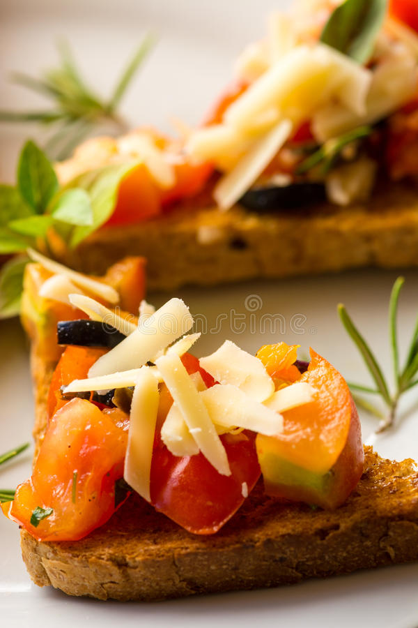 Bruschetta - typical Italian food. Bruschetta with sliced tomatoes salad and olive with herb topping royalty free stock images