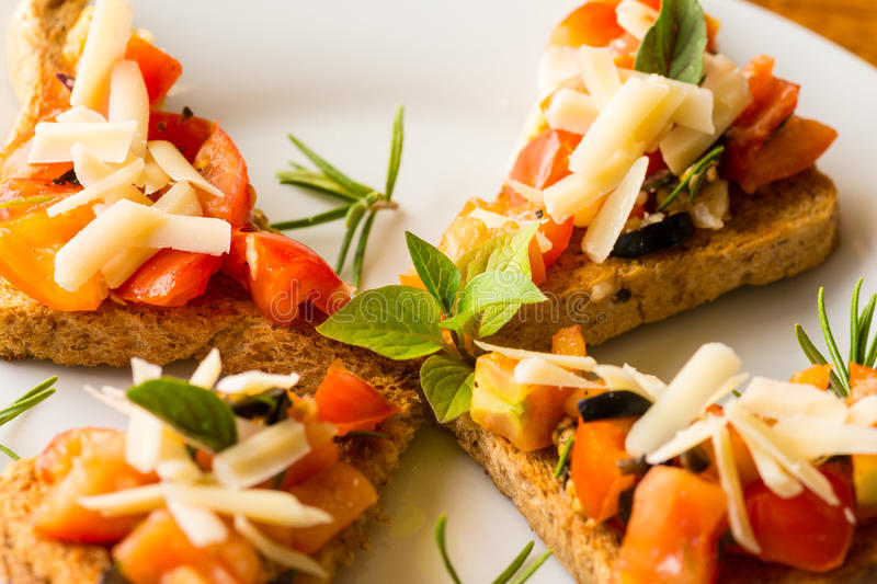 Bruschetta - typical Italian food. Bruschetta with sliced tomatoes salad and olive with herb topping royalty free stock image