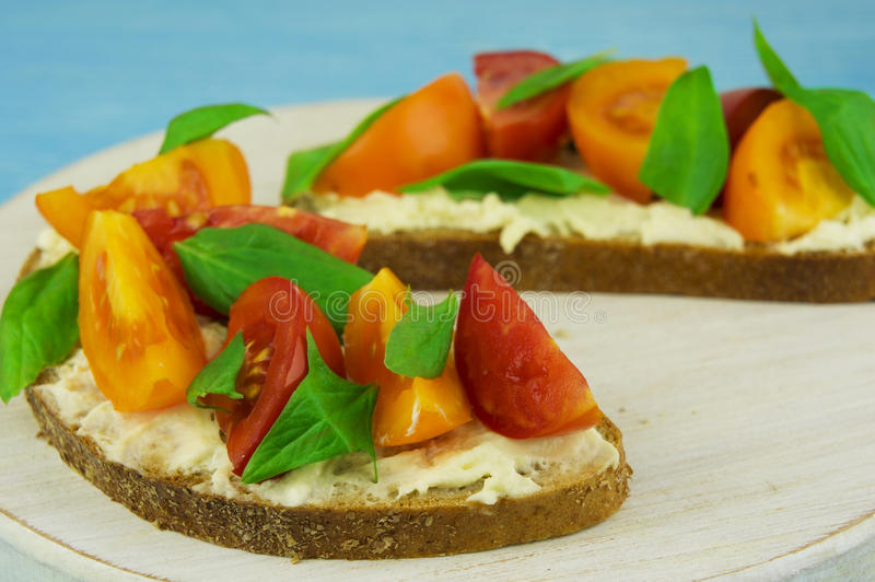 Bruschetta with soft cheese, basil and cherry tomatoes on a wood stock photography