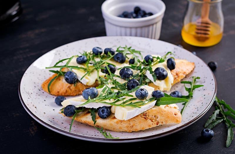 Bruschetta. Toast crostini with fresh berries blueberry and honey, brie cheese, arugula. royalty free stock photo