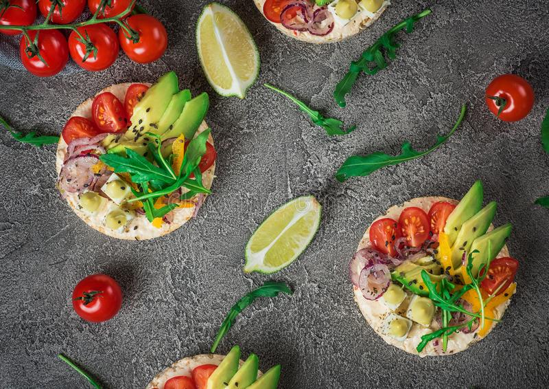 Bruschetta with tomato, avocado, herbs and arugula. Rustic background. Top view royalty free stock image