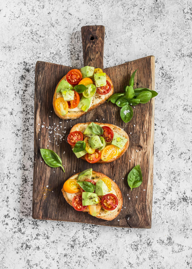 Bruschetta with tomatoes and avocado on rustic wooden cutting board. Delicious snack royalty free stock image