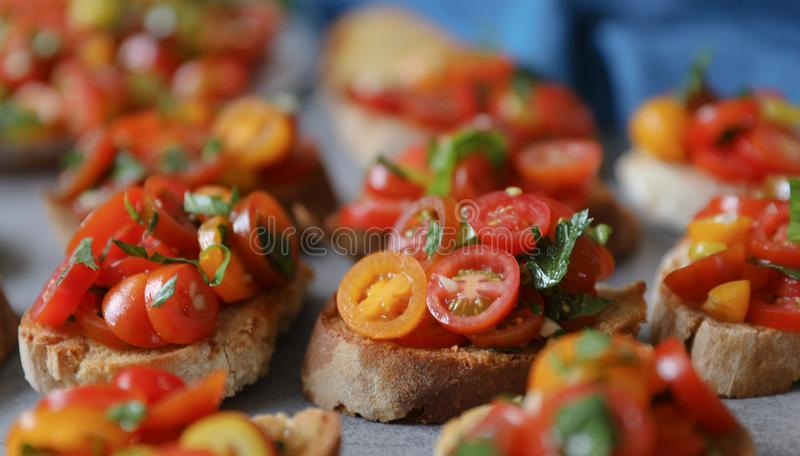 Bruschetta with tomatoes, basil and parsley,  an Italian delicious savory  appetizer. Background, Italian cuisine concept. Close up view, selective focus stock photography