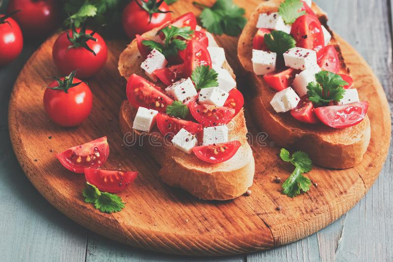 Bruschetta with tomatoes, cheese and cilantro on a cutting wooden board, rustic table. Selective focus, toned image royalty free stock photography