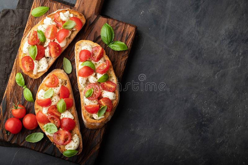 Bruschetta with tomatoes, mozzarella cheese and basil on a cutting board. Traditional italian appetizer or snack, antipasto. Top v. Iew with copy space. Flat lay stock photo