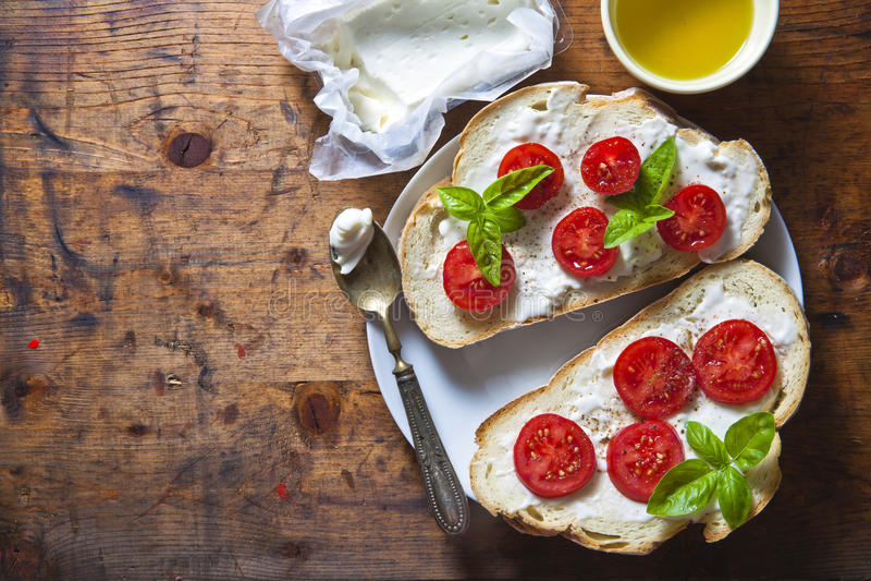 Bruschetta z miękkim serem, basilem i czereśniowymi pomidorami na drewnie, fotografia stock