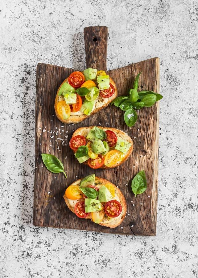Bruschetta z pomidorami i avocado na nieociosanej drewnianej tnącej desce wyśmienicie przekąska obraz royalty free