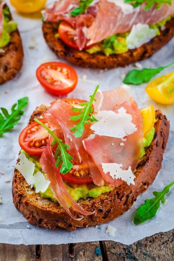Bruschetta z prosciutto, avocado, pomidorami, arugula i serem, obrazy stock