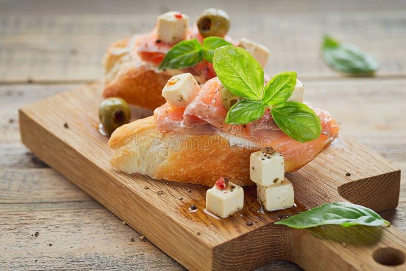 Bruschetta z uwędzonym łososiem, kremowym serem, oliwkami i arugula, fotografia royalty free
