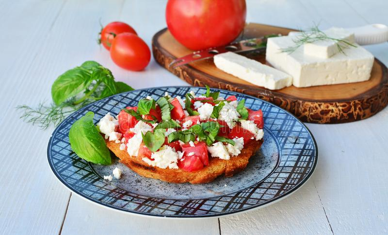 Bruschettas del tomate con queso y albahaca de cabra en la placa fotos de archivo libres de regalías