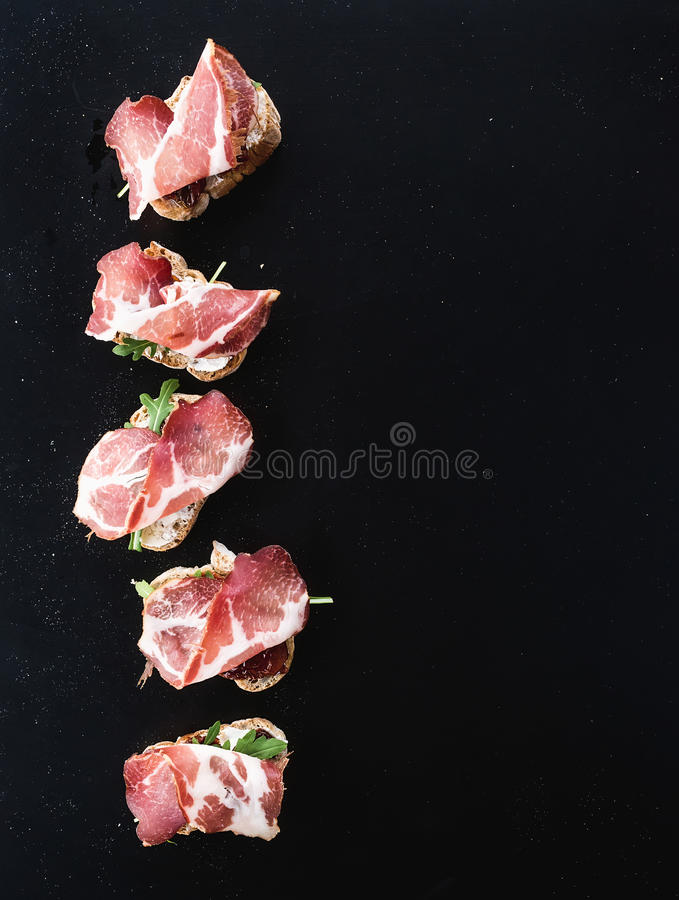 Bruschettas med prosciutto rökt kött som torkas royaltyfria bilder