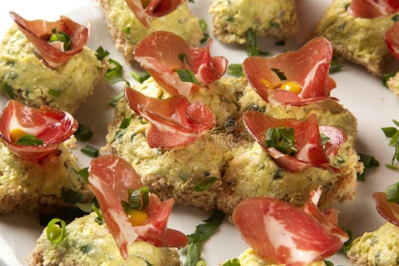 Bruschettas med prosciutto rökt kött, torkade tomater arkivbilder