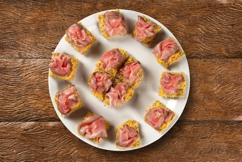 Bruschettas med prosciutto rökt kött, torkade tomater royaltyfri fotografi