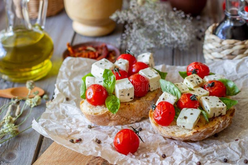 Bruschettas with tomatoes and cheese. Italian cuisine. Rustic style. Vegetarian food. Bruschettas with tomatoes and cheese. Italian cuisine. Simple style stock photography