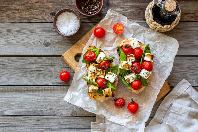 Bruschettas with tomatoes and cheese. Italian cuisine. Rustic style. Vegetarian food. Bruschettas with tomatoes and cheese. Italian cuisine. Simple style stock photo