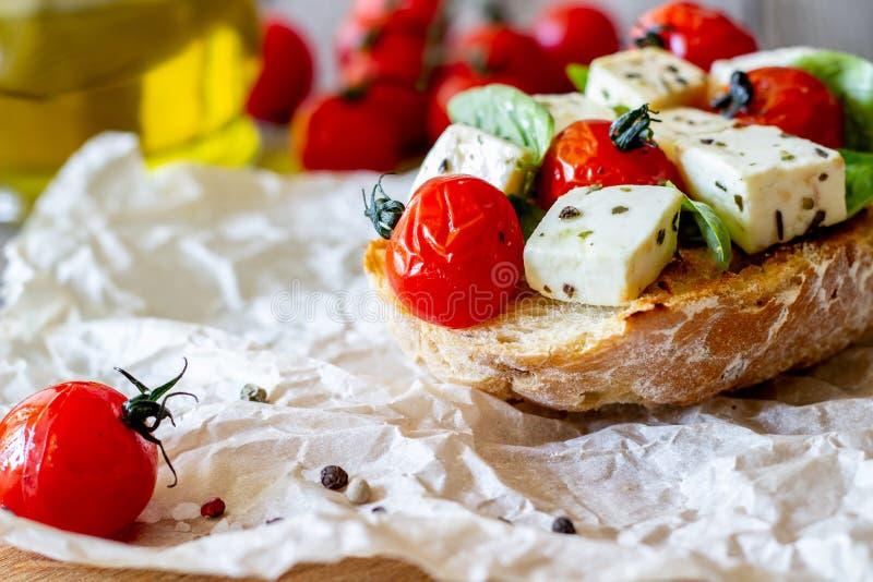 Bruschettas with tomatoes and cheese. Italian cuisine. Rustic style. Vegetarian food. Bruschettas with tomatoes and cheese. Italian cuisine. Simple style royalty free stock image