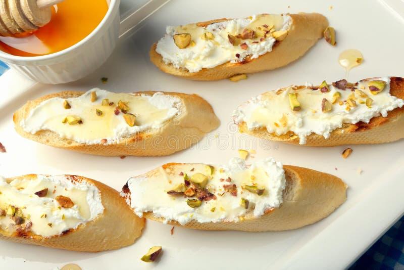 Bruschettasandwich met de honing en de pistaches van de geitkaas stock afbeelding