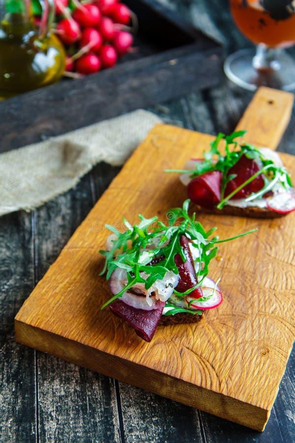 Bruschette avec des betteraves, des poissons et des oignons sur une planche à découper images stock