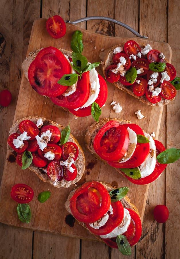 Bruschette avec du fromage, les tomates, le basilic frais et le vinaigre balsamique sur la planche à découper, vue supérieure photographie stock libre de droits