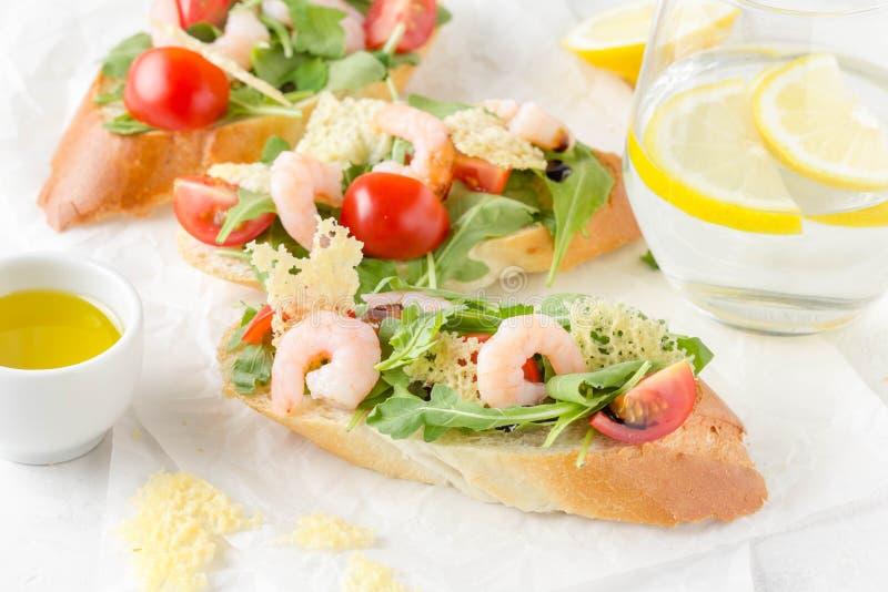 Bruschette avec l'arugula, la crevette, les tomates-cerises et le vinaigre balsamique Trois sandwichs ouverts savoureux pour le d photographie stock
