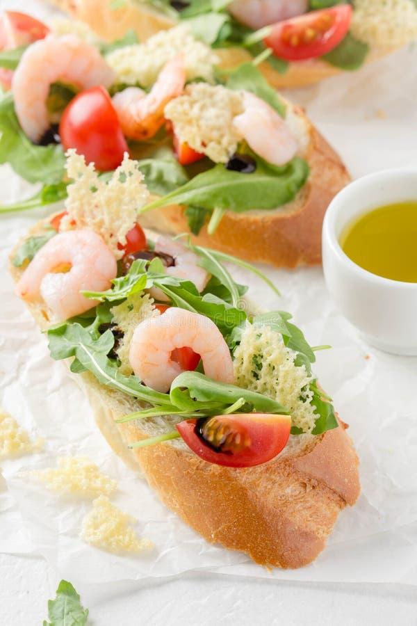 Bruschette avec l'arugula, la crevette, les tomates-cerises et le vinaigre balsamique Trois sandwichs ouverts savoureux pour le d images libres de droits