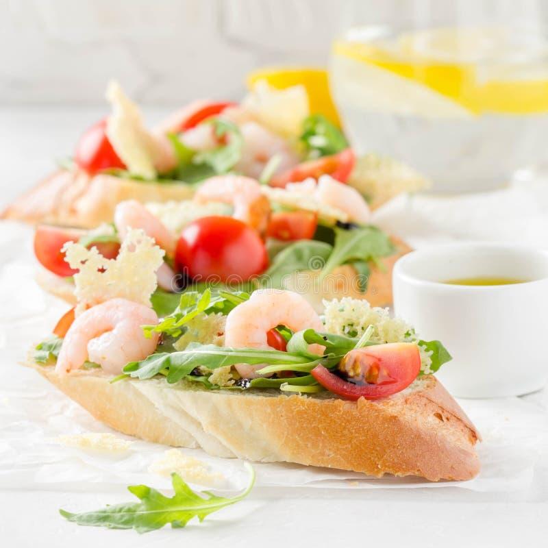 Bruschette avec l'arugula, la crevette, les tomates-cerises et le vinaigre balsamique Trois sandwichs ouverts savoureux pour le d images stock