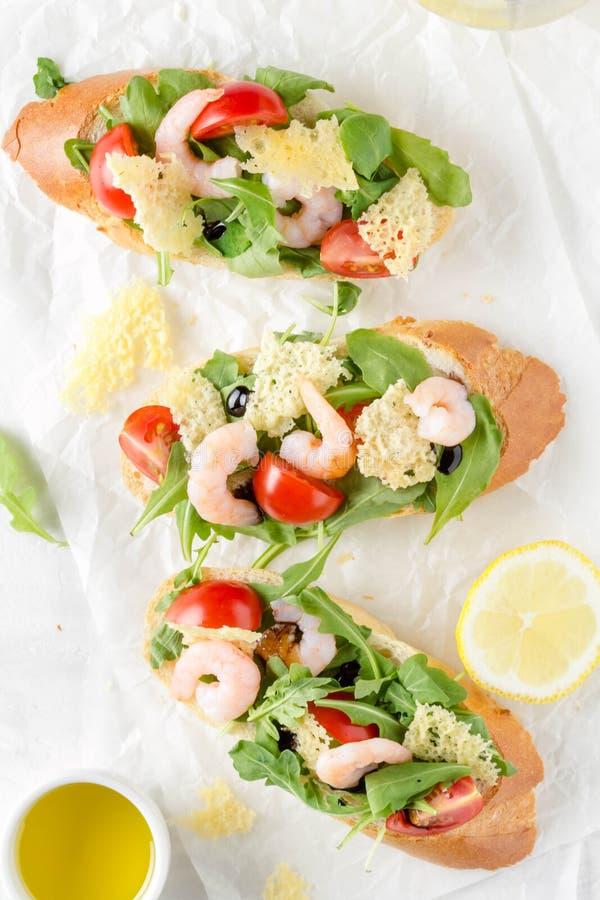 Bruschette avec l'arugula, la crevette, les tomates-cerises et le vinaigre balsamique Trois sandwichs ouverts savoureux pour le d photo libre de droits