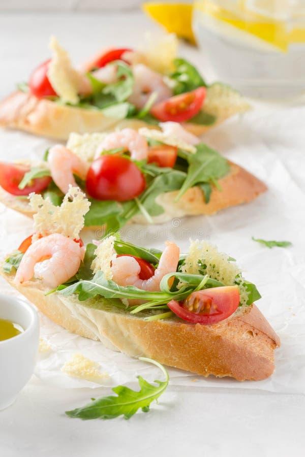 Bruschette avec l'arugula, la crevette, les tomates-cerises et le vinaigre balsamique Trois sandwichs ouverts savoureux pour le d image stock